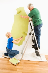 Man and woman painting wall.